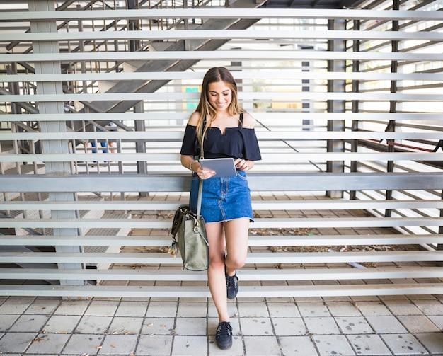 Młoda kobieta z torbą używać pastylkę w uniwersytecie