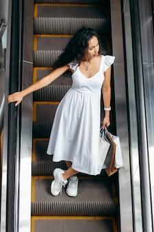 Młoda kobieta z torbami na schodach ruchomych