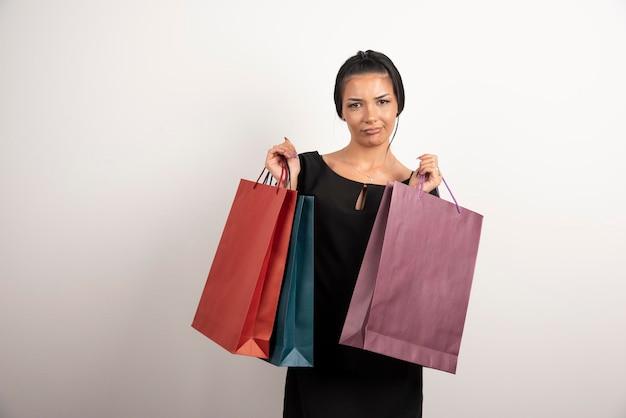 Młoda kobieta z torby na zakupy pozuje na białej ścianie.