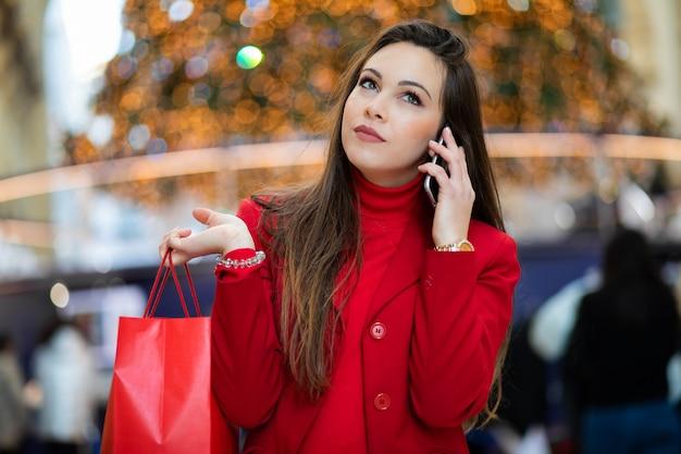 Młoda kobieta z torby na zakupy w mediolanie, włochy, rozmawia przez telefon