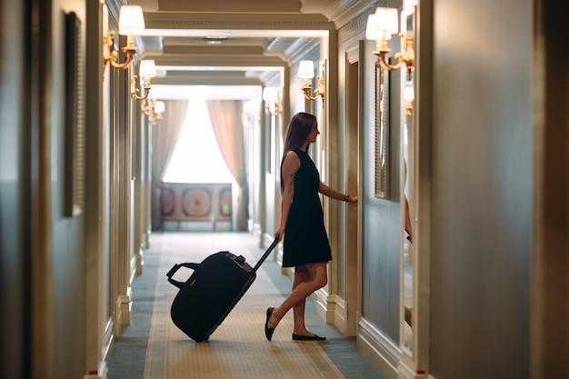 Młoda kobieta z torebką i walizką w eleganckim garniturze idzie korytarzem do swojego pokoju.