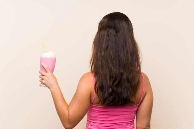 Młoda kobieta z truskawkowym koktajlem mlecznym w tylnej pozycji