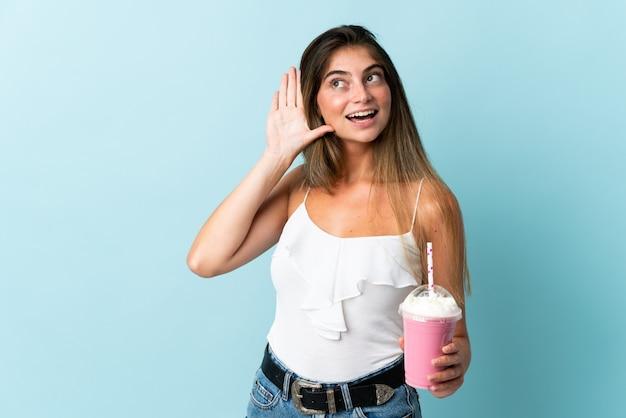Młoda kobieta z truskawkowym koktajlem na białym tle na niebiesko słuchając czegoś, kładąc rękę na uchu