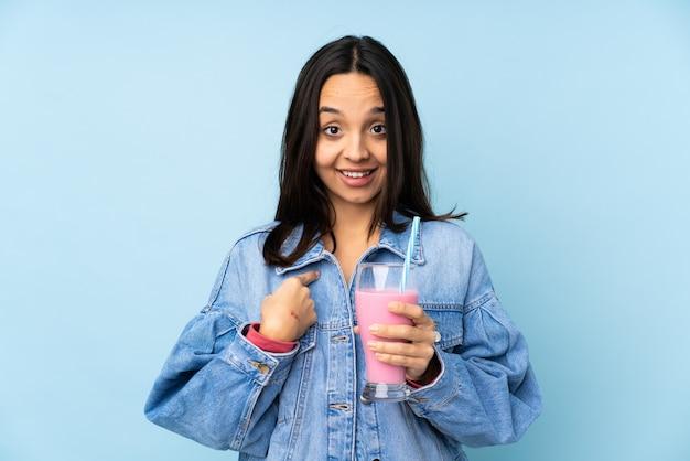 Młoda kobieta z truskawkowym milkshake z niespodzianka wyrazem twarzy