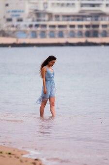 Młoda kobieta z turkusową sukienką spacerując po plaży
