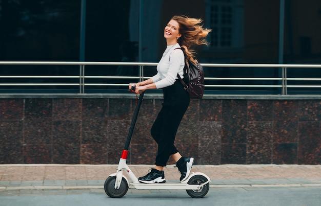 Młoda kobieta z uśmiechem jeździć skuter elektryczny na ulicy