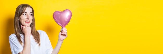Młoda kobieta z uśmiechem trzyma w rękach balon w kształcie serca i patrzy na niego na żółtym tle. transparent.