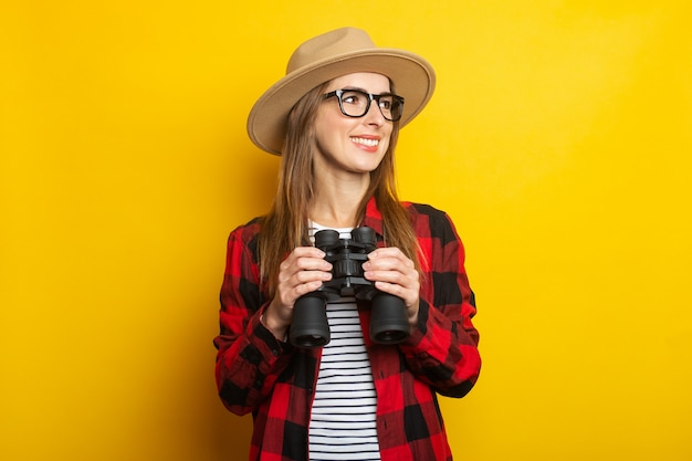 Młoda kobieta z uśmiechem w kapeluszu i koszuli w kratę, trzymając w rękach lornetkę na żółtej powierzchni