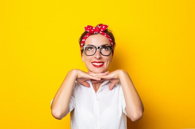 Młoda kobieta z uśmiechem, w okularach i czerwonej opasce na głowie na żółtej ścianie.