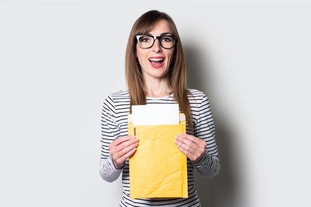 Młoda kobieta z uśmiechem wyjmuje list lub zawiadomienie z papierowej koperty