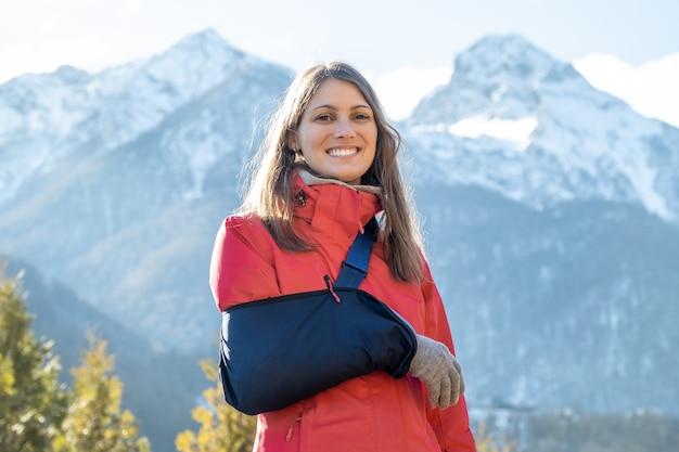 Młoda kobieta z uszkodzoną prawą ręką po jeździe na snowboardzie