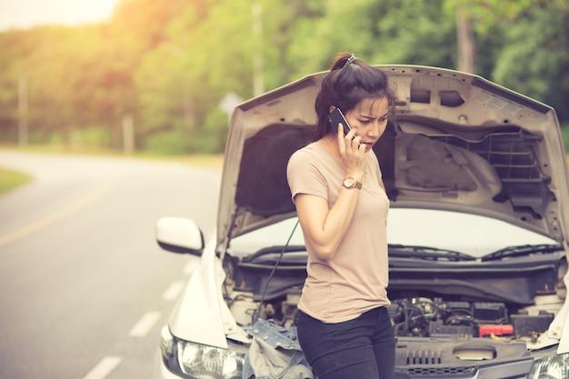 Młoda kobieta z uszkodzony samochód woła o pomoc. vintage kolor
