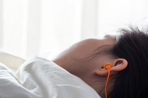 Młoda kobieta z uszy na uszy do spania na łóżku