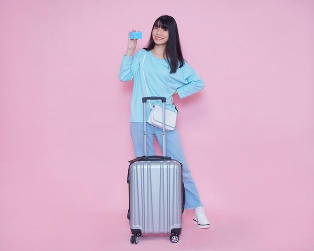Młoda kobieta z walizką i kartą kredytową na ścianie koloru