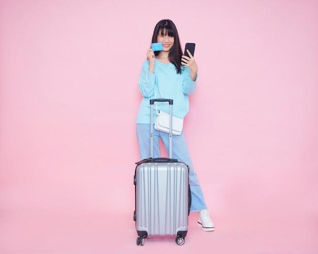 Młoda kobieta z walizką i przy użyciu telefonu komórkowego z kartą kredytową do płacenia.