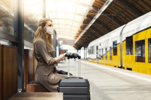 Młoda kobieta z walizką, ubrana w maskę i rękawiczki i czekająca na stacji kolejowej