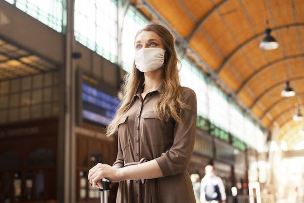 Młoda kobieta z walizką w masce na twarzy i czekająca na dworcu – covid-19