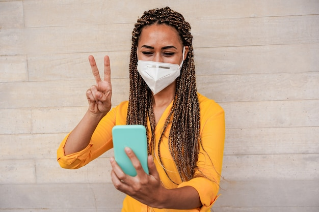 Młoda kobieta z warkoczami robi rozmowę wideo podczas gdy jest ubranym maskę ochronną twarzy dla zapobiegania koronawirusowi