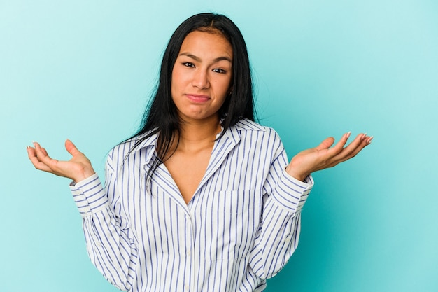 Młoda kobieta z wenezueli na białym tle na niebieskim tle, wątpiąc i wzruszając ramionami w geście przesłuchania.