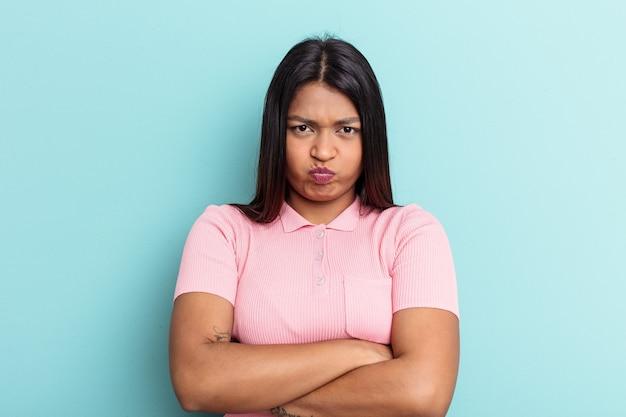 Młoda kobieta z wenezueli na niebieskim tle dmucha w policzki, ma zmęczony wyraz twarzy. koncepcja wyraz twarzy.