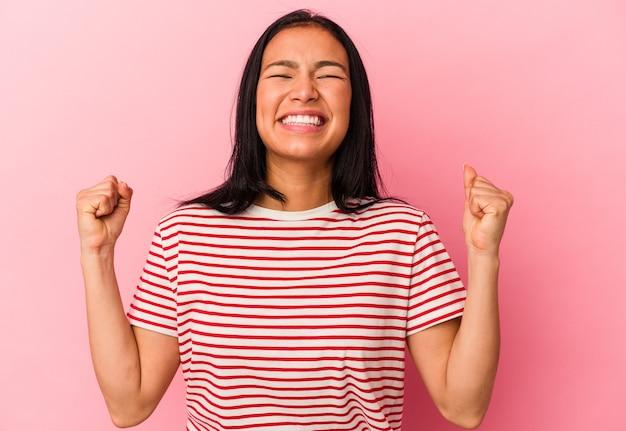 Młoda kobieta z wenezueli na różowej ścianie świętuje zwycięstwo, pasję i entuzjazm, szczęśliwy wyraz.
