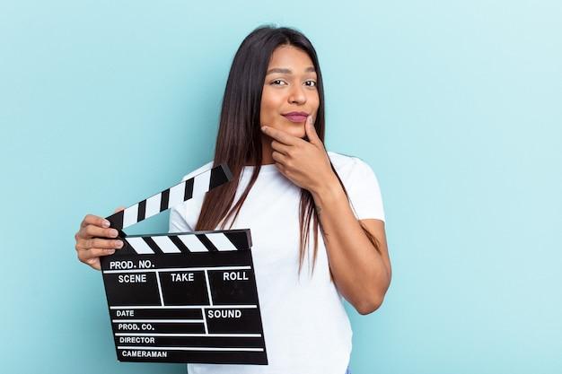 Młoda kobieta z wenezueli trzymając klaps na białym tle na niebieskim tle patrząc w bok z wyrazem wątpliwości i sceptyczny.