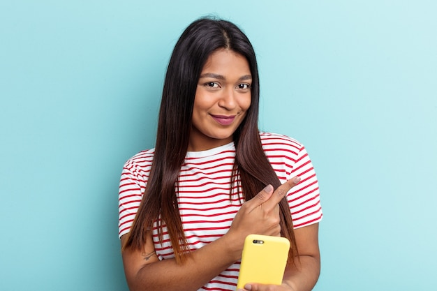 Młoda kobieta z wenezueli trzymająca telefon komórkowy na białym tle na niebieskim tle, uśmiechając się i wskazując na bok, pokazując coś w pustej przestrzeni.