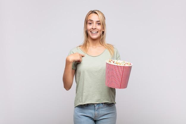 Młoda kobieta z wiaderkiem popcornu czuje się szczęśliwa, zaskoczona i dumna, wskazując na siebie z podekscytowanym, zdziwionym spojrzeniem