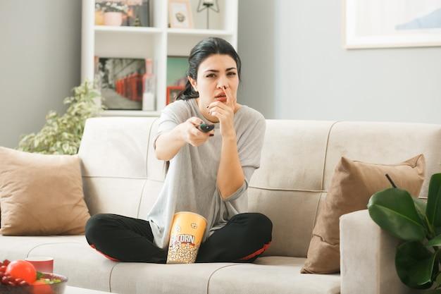 Młoda kobieta z wiadrem popcornu trzymająca pilota od telewizora do kamery, siedząca na kanapie za stolikiem kawowym w salonie