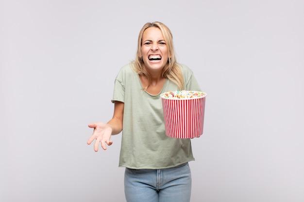 Młoda kobieta z wiadrem z popcornami wygląda na wściekłą, zirytowaną i sfrustrowaną, krzyczy wtf lub co jest z tobą nie tak