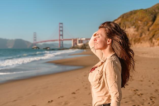 Młoda kobieta z widokiem na most golden gate w san francisco