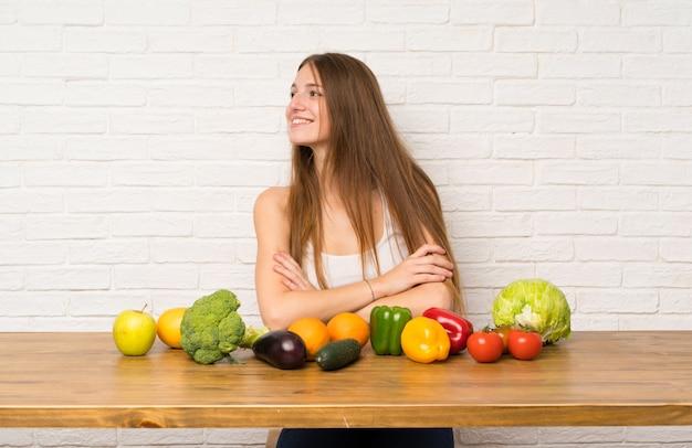 Młoda kobieta z wieloma warzywami stoi i patrzeje strona
