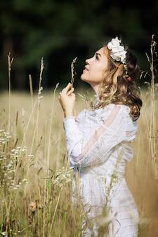 Młoda kobieta z wieńcem na głowie w białej sukni w stylu boho w terenie