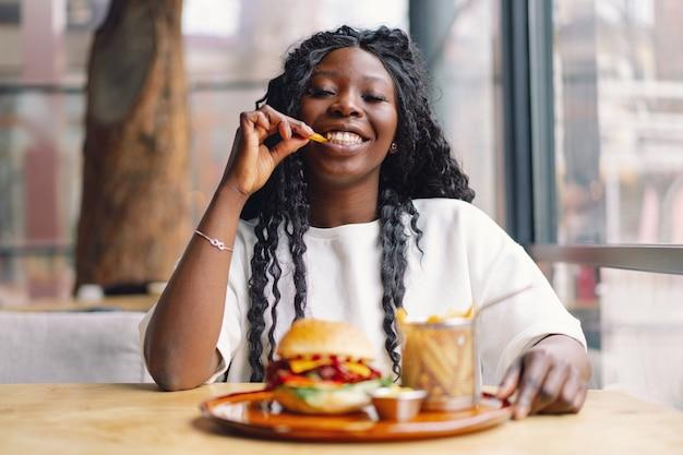 Młoda kobieta z włosami afro je smacznego klasycznego burgera z frytkami