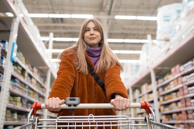 Młoda kobieta z wózek sklepowy i półki z sklepami spożywczymi w sklepie