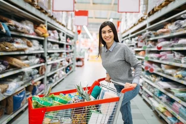 Młoda kobieta z wózkiem pełnym towarów w supermarkecie, zakupy. kobieta klient w sklepie, kupujący na rynku