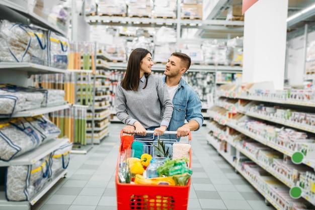 Młoda kobieta z wózkiem pełnym towarów w supermarkecie