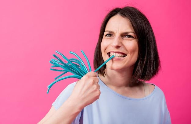 Młoda kobieta z wrażliwymi zębami je słodkie cukierki na kolorowym tle