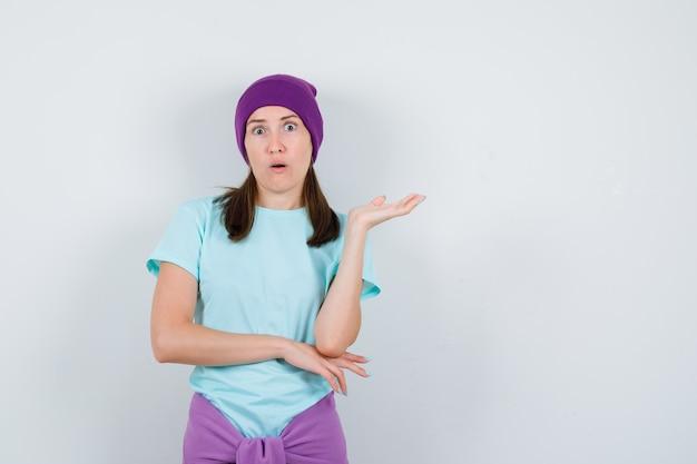 Młoda kobieta z wyciągniętą dłonią, trzymająca otwarte usta w niebieskiej koszulce, fioletowej czapce i wyglądająca na zaskoczoną, widok z przodu.
