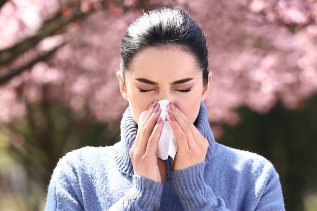 Młoda kobieta z wycieraczką do nosa w pobliżu kwitnącego drzewa