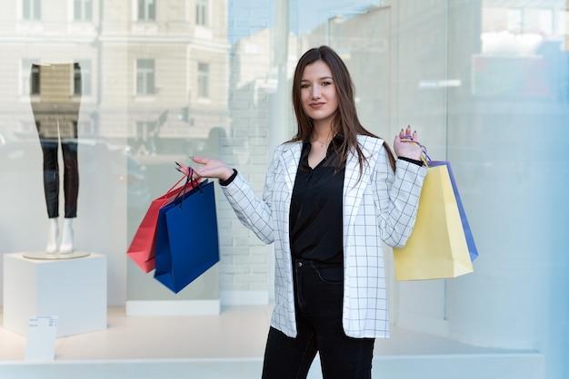 Młoda kobieta z zakupami po zakupach w oknie sklepu
