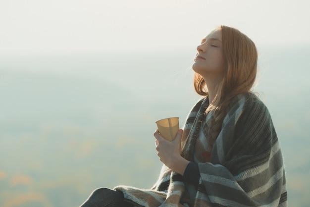 Młoda kobieta z zamkniętymi oczami cieszy się powietrzem. kubek papierowy w ręce, słoneczny dzień