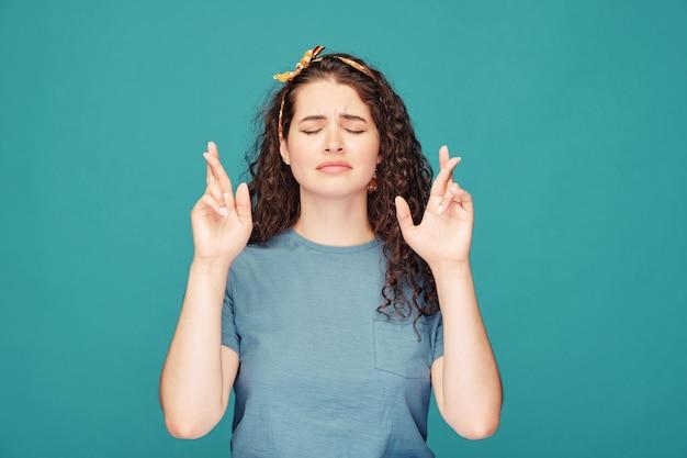 Młoda kobieta z zamkniętymi oczami krzyżuje palce, mając nadzieję na szczęście, niebieski
