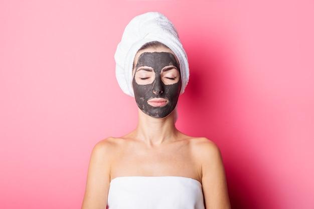 Młoda kobieta z zamkniętymi oczami z czarną maską na różowym tle