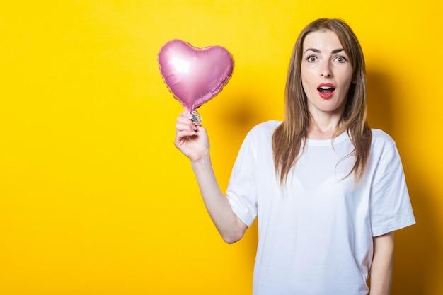 Młoda kobieta z zaskoczoną twarzą trzyma w rękach balon w kształcie serca na żółtym tle. transparent.