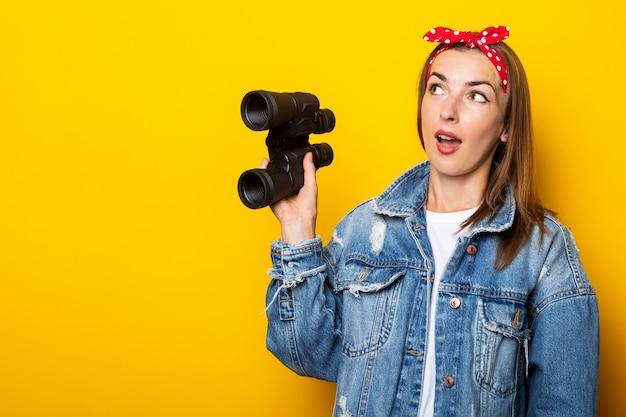 Młoda kobieta z zaskoczoną twarzą w dżinsach i tratwą na głowie trzyma lornetkę w dłoniach na żółtej ścianie. transparent.