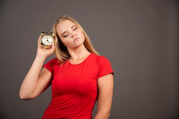 Młoda kobieta z zegarem do spania na czarnej ścianie.