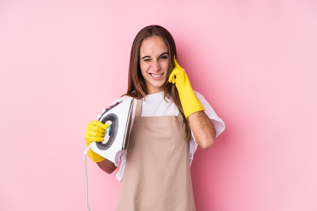 Młoda kobieta z żelaza ubrania na białym tle obejmujące uszy rękami
