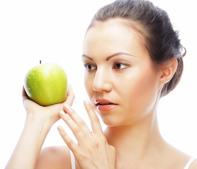 Młoda kobieta z zielonym jabłkiem odizolowywającym na białym tle