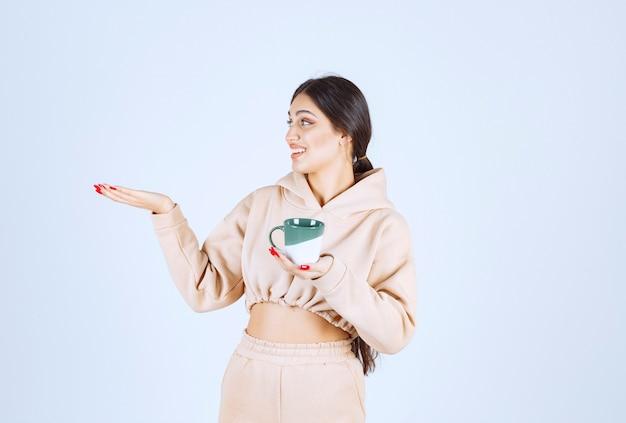 Młoda kobieta z zielonym kubkiem wskazującym gdzieś po lewej stronie